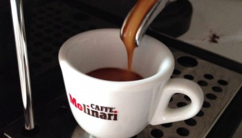 pouring coffee into a caffe molinari cup